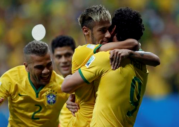 Brazil's Fred (R) celebrates his goal against Cameroon with teammates Neymar (2nd R) and Daniel Alves (L) during their 2014 World Cup Group A soccer match at the Brasilia national stadium in Brasilia June 23, 2014.