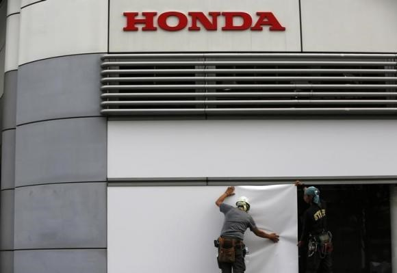 Workers stand under the logo of Honda Motor Co. outside the company's headquarters in Tokyo October 30, 2013.