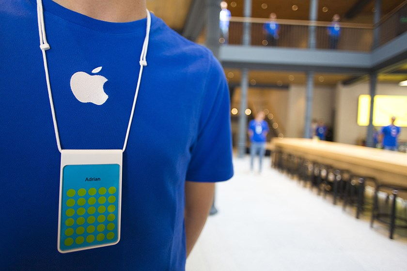 An employee wears a blue Apple-branded t-shirt and name badge during a media briefing at Apple Inc.'s new Spanish flagship store on Puera de Sol square the day before opening to the public in Madrid, Spain.