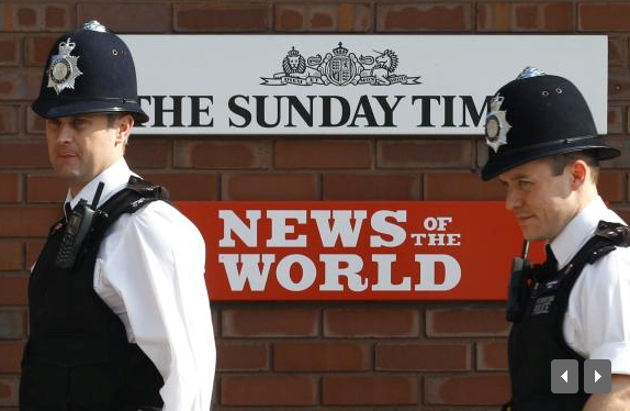 Police officers stand outside an entrance to News International in London in this July 10, 2011 file photo.