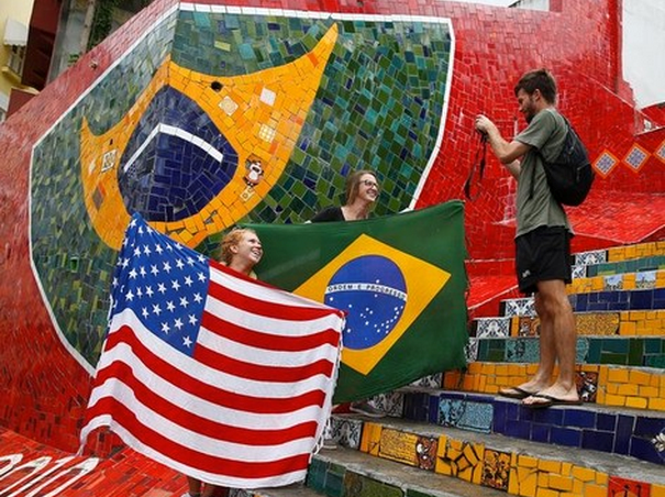 Tourists pose with a U.S. and Brazilian flag ahead of the 2014 World Cup in Rio de Janeiro, June 10, 2014.