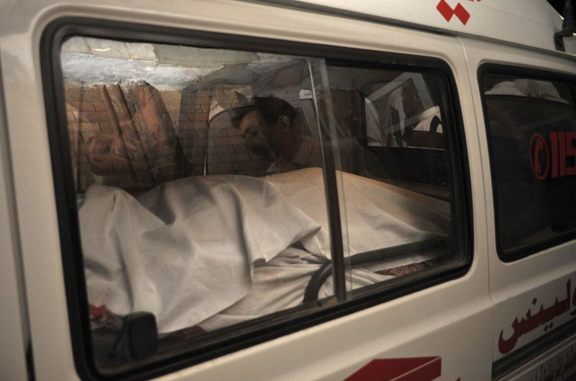 The body of a passenger killed in a shooting is placed in an ambulance at Peshawar airport in Pakistan.