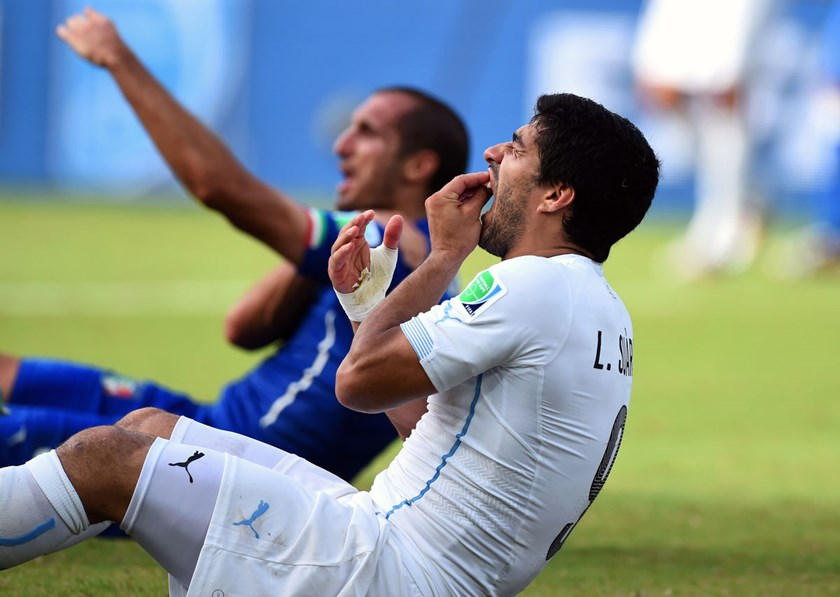 Luis Suarez of Uruguay, right, and Giorgio Chiellini of Italy react after a clash during the 2014 FIFA World Cup Group D match at Estadio das Dunas in Natal, Brazil, on June 24, 2014.