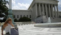 A woman uses her mobile phone at the plaza of the U.S. Supreme Court in Washington June 25, 2014.