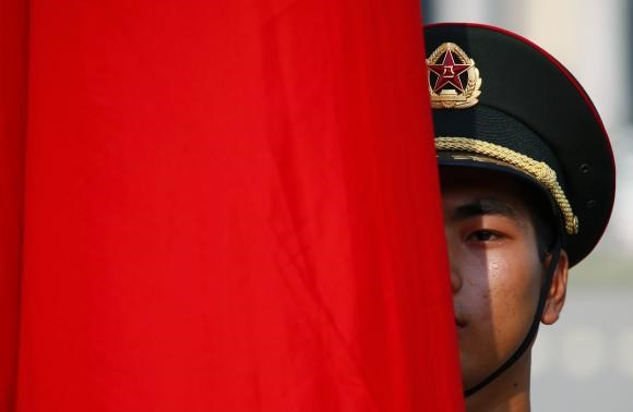 An honour guard member is seen behind a red flag during a welcoming ceremony for Kuwait's Prime Minister Sheikh Jaber al-Mubarak al-Sabah at the Great Hall of the People in Beijing, June 3, 2014.