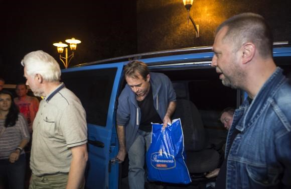 Unidentified members of OSCE Special Monitoring Mission in Ukraine get out of a vehicle next to Alexander Borodai (R), Prime Minister of the self proclaimed ''Donetsk People's Republic'', on arrival at the city of Donetsk after being released from captivi