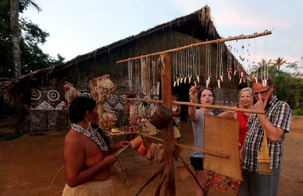 Tourists look at crafts made by members of the Amazonian Tatuyo tribe in their village June 23, 2014.
