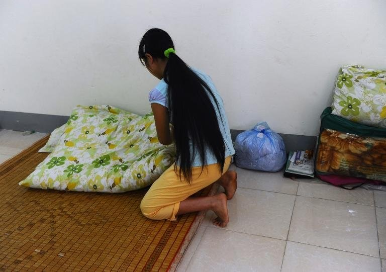 H'mong ethnic girl Kiab (whose name has been changed to protect her identity) makes her bed at a government-run centre for trafficked women in the northern city of Lao Cai, May 9, 2014. Photo credit: Hoang Dinh Nam/AFP