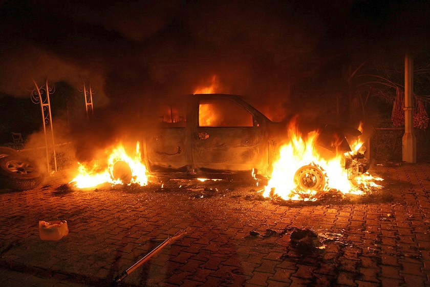 A vehicle and the surrounding area are engulfed in flames after it was set on fire inside the US consulate compound in Benghazi on Sept. 11, 2012. Photo credit: AFP