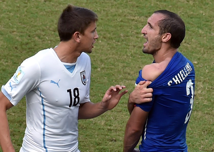 Italy's defender Giorgio Chiellini, right. shows an apparent bitemark by Uruguay forward Luis Suarez to Uruguay's midfielder Gaston Ramirez, left, during a Group D football match between Italy and Uruguay at the Dunas Arena in Natal during the 2014 FIFA W