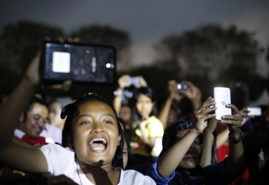 Youths take pictures during music concert held in support for Indonesia's presidential candidate Joko Widodo in Jakarta June 25, 2014.