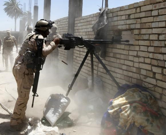 A member of the Iraqi security forces opens fire during clashes with fighters from Sunni militant group Islamic State of Iraq and the Levant (ISIL) in Ibrahim bin Ali village, west of Baghdad, June 24, 2014.