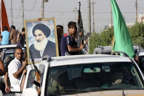Volunteers, who have joined the Iraqi Army to fight against predominantly Sunni militants, carry weapons and a portrait of Grand Ayatollah Ali al-Sistani during a parade in the streets in Baghdad's Sadr city June 14, 2014.