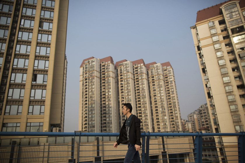 A man walks past residential buildings in the Pazhou district of Guangzhou. After four years of government restrictions to cool the housing market, home sales and property construction are sliding and have become a drag on the economy, which expanded at t