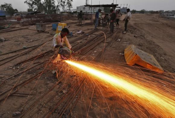 A labourer cuts an iron rod at the construction site of a flyover on the outskirts of the western Indian city of Ahmedabad June 24, 2014.