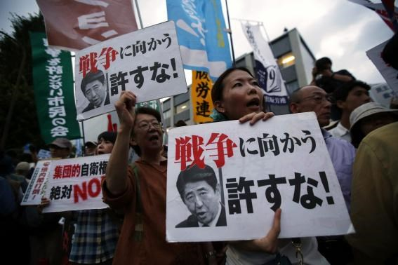 Protesters shout slogans as they hold placards during a rally against Japan's Prime Minister Shinzo Abe's push to expand Japan's military role, in front of Abe's official residence in Tokyo July 1, 2014.