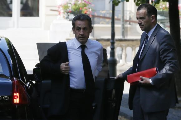 Former French President Nicolas Sarkozy (L) arrives at the National Assembly in Paris June 25, 2014.