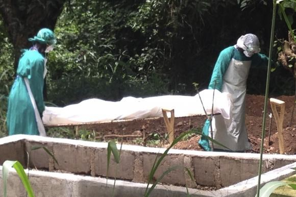 Health workers carry the body of an Ebola virus victim in Kenema, Sierra Leone, June 25, 2014.
