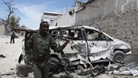 A Somali government soldier walks next to a car damaged in an explosion near Al Mukaram Hotel in Mogadishu March 15, 2014.
