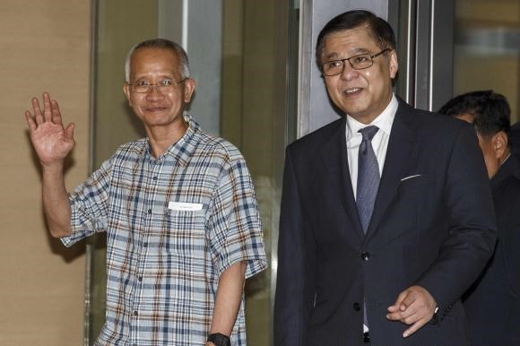 Veera Somkwamkid (L), a Thai ultra-nationalist jailed for eight years for espionage and trespassing and accompanied by Acting Thai Foreign Minister Sihasak Phuangketkeow arrives at Bangkok's Suvarnabhumi International Airport July 2, 2014.