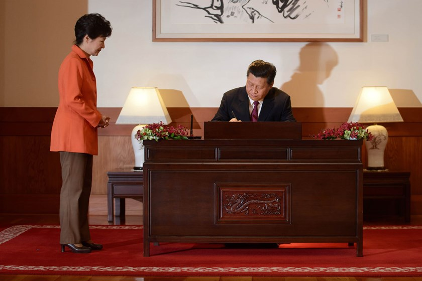 China's President Xi Jinping, right, signs a guest book as his South Korean counterpart Park Geun-Hye looks on prior to a summit meeting in Seoul on July 3, 2014. Xi and Park agreed to set up direct won-yuan trading, conclude free trade talks between thei