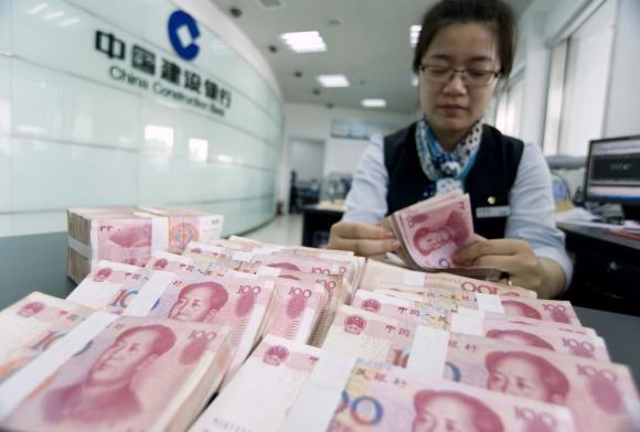 A clerk counts Chinese 100 yuan banknotes at a branch of China Construction Bank in Hai'an, Jiangsu province June 10, 2014.
