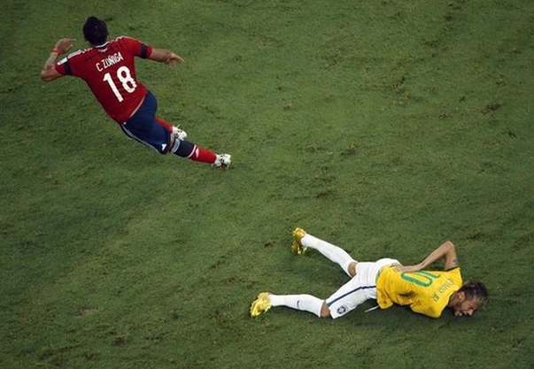 Brazil's Neymar grimaces as he lies on the ground injured after a challenge by Colombia's Camilo Zuniga during their 2014 World Cup quarter-finals at the Castelao arena in Fortaleza July 4, 2014.
