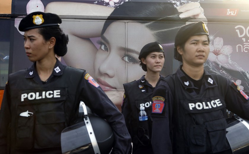 A beauty product advertisement on a passing bus is seen as Thai female riot police take positions to prevent demonstrations against military rule at Victory Monument in Bangkok.