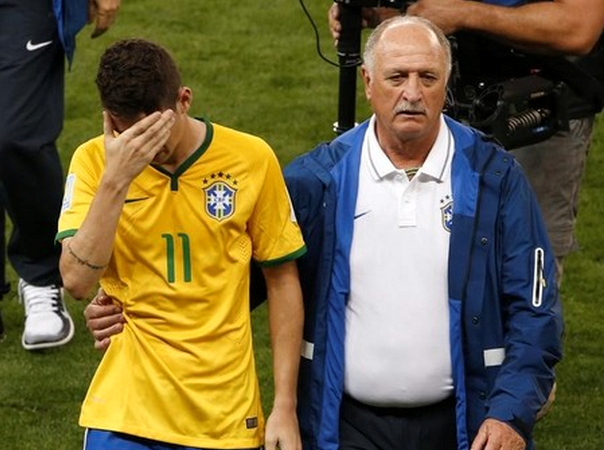 Brazil's Oscar (L) is comforted by coach Luiz Felipe Scolari after they lost their 2014 World Cup semi-finals against Germany at the Mineirao stadium in Belo Horizonte July 8, 2014.
