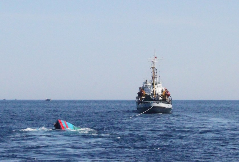 A Vietnamese boat (left), which was rammed and then sunk by Chinese vessels, is seen near a Coast Guard ship. Vietnamese authorities said some 40 Chinese fishing boats surrounded the Vietnamese craft before one of them rammed it and it sank in late May. V