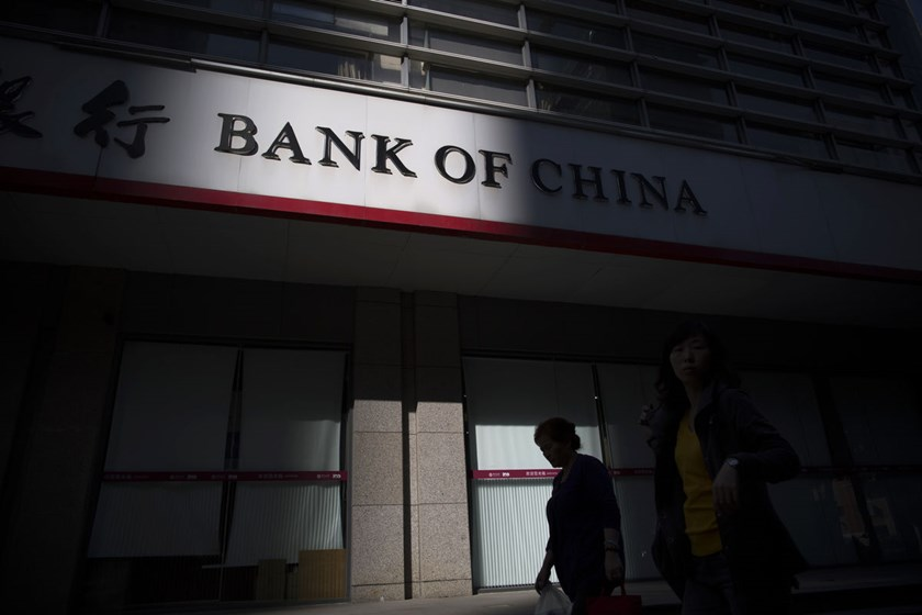 Pedestrians walk past a branch of Bank of China Ltd. in Guangzhou, China. China's policy makers have taken steps in recent years including allowing freer movements of capital in and out of the country as they seek to boost the global stature of the yuan.