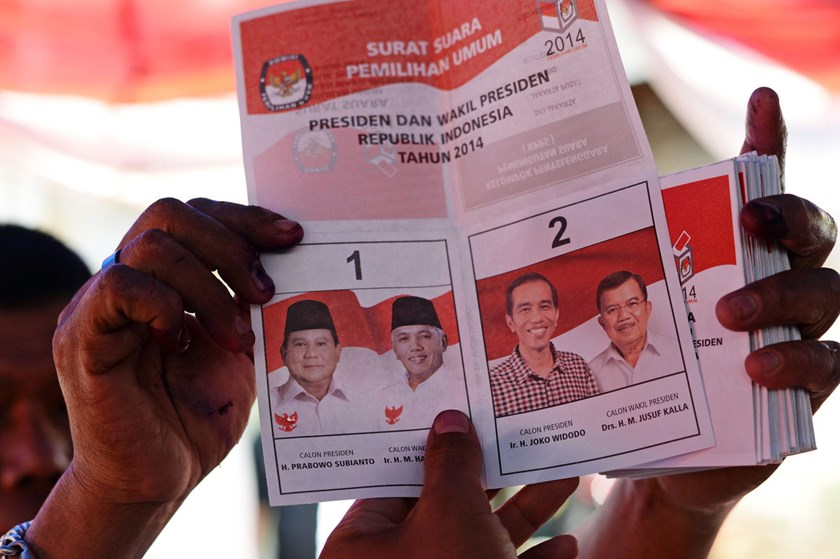 An official holds up a ballot paper during vote counting following the presidential election in Jakarta. Before the election commission can release official results by July 22, it must tally the ballots of the forecast 75 percent of 190 million eligible v