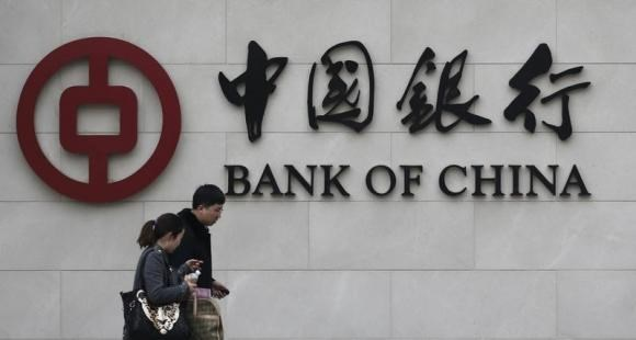Pedestrians walk past a Bank of China sign at its branch in Beijing March 26, 2013.