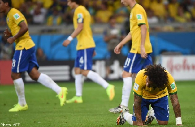 Brazil's defender Marcelo reacts after unseen Germany's forward Andre Schuerrle scored during the semi-final football match between Brazil and Germany at The Mineirao Stadium in Belo Horizonte on July 8, 2014, during the 2014 FIFA World Cup. Photo credit: