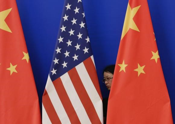 A member of staff from Chinese government adjusts U.S. and Chinese national flags before a news conference for the 6th round of U.S.-China Strategic and Economic Dialogue at the Great Hall of the People in Beijing, July 10, 2014.