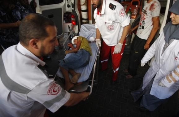 Palestinian medics wheel a stretcher transporting a boy, who hospital officials said was wounded in an Israeli air strike, at a hospital in Gaza City July 11, 2014.
