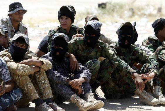 Shi'ite volunteers, who have joined the Iraqi army to fight against militants of the Islamic State, formerly known as the Islamic State of Iraq and the Levant (ISIL), sit together during training in Baghdad, July 9, 2014.