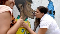 Fans kiss a graffiti depicting footballer Neymar kissing goodbye the ghost of the Maracanazo (the defeat of Brazil by the winning Uruguayan team in the 1950 World Cup) in Rio de Janeiro. Photo credit: AFP