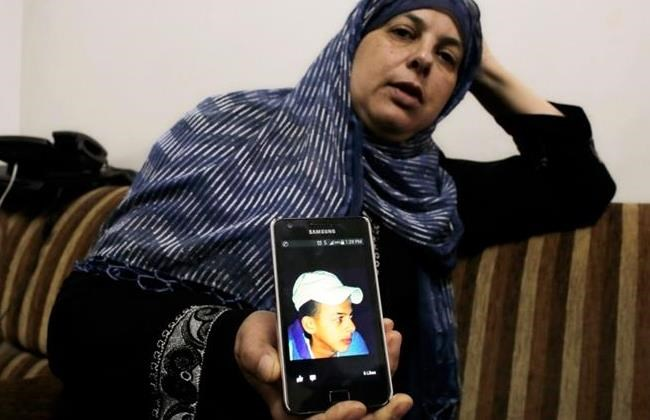 Suha, mother of Mohammed Abu Khudair, shows a picture of her son on her mobile phone at their home in Shuafat, an Arab suburb of Jerusalem July 2, 2014.