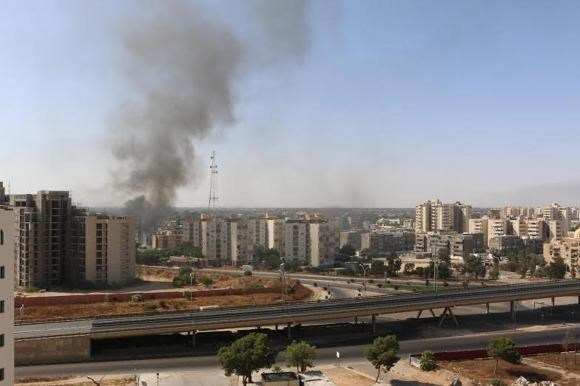 Smoke rises near buildings after heavy fighting between rival militias broke out near the airport in Tripoli July 13, 2014.