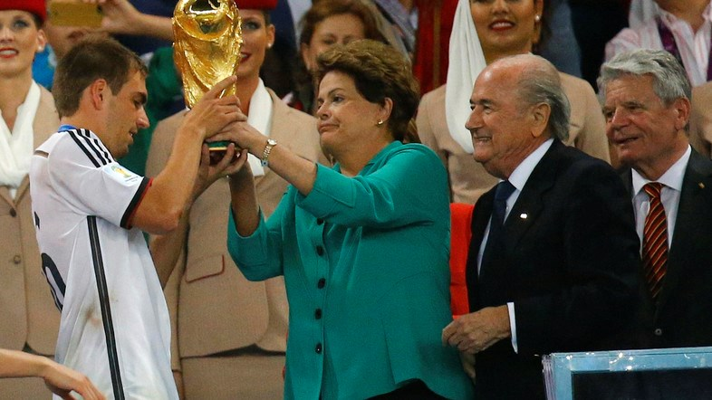 Brazil's President Dilma Rousseff (2nd L), FIFA President Sepp Blatter (2nd R) and German President Joachim Gauck (R) watch as Germany's Philipp Lahm lifts the World Cup trophy after winning the 2014 World Cup final against Argentina at the Maracana stadi