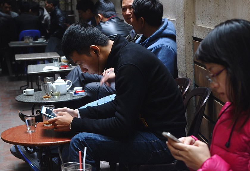 Customers use wireless devices at a coffee shop in downtown Hanoi.