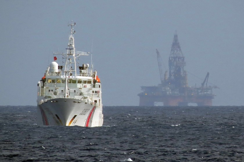 A Chinese marine surveillance vessel sail in the South China Sea. In the background is an oil rig China illegally deployed in Vietnam's exclusive economic zone in May 2014.