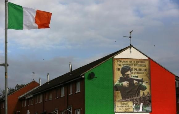 An Irish flag flies beside a mural in the Ardoyne area of North Belfast displaying an image of a I.R.A. gunman November 5, 2013.