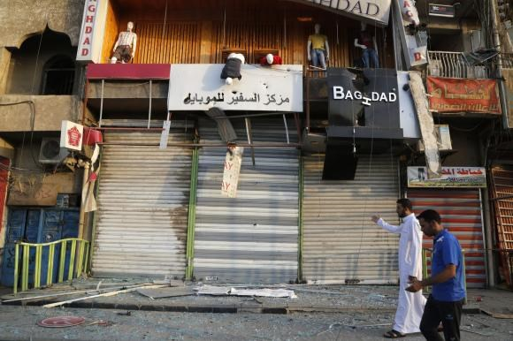 Residents inspect the site of bomb attack at a market in Baghdad's Sadr City, July 16, 2014.