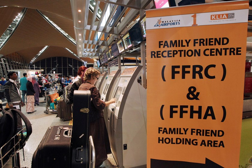 Passengers use self-service kiosks to check in as a sign directs family and friends of passengers onboard Malaysia Airlines Flight 17 to a holding area at Kuala Lumpur International Airport (KLIA) in Sepang, Malaysia, on Friday, July 18, 2014.