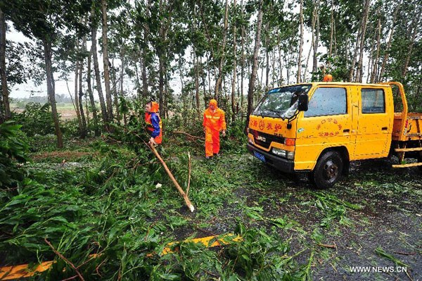 Municipal workers clear tree branches off the road in Wenchang, south China's island of Hainan Province, July 18, 2014. Photo credit: Xinhua