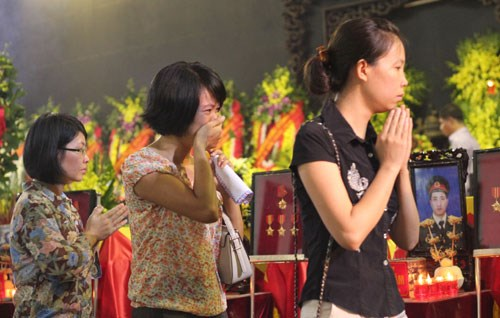 Family members and relatives pay tribute at the collective funeral of 18 soldiers who died in a helicopter crash in Hanoi this month.
