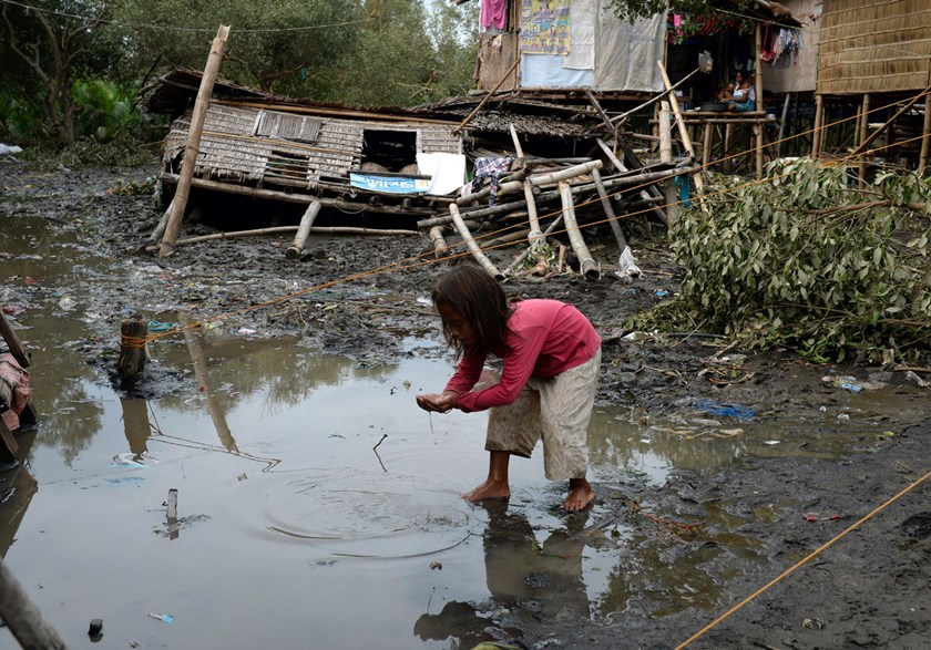 A child plays in water next to a house destroyed by Typhoon Rammasun in Batangas, southwest of Manila, on July 17, 2014.