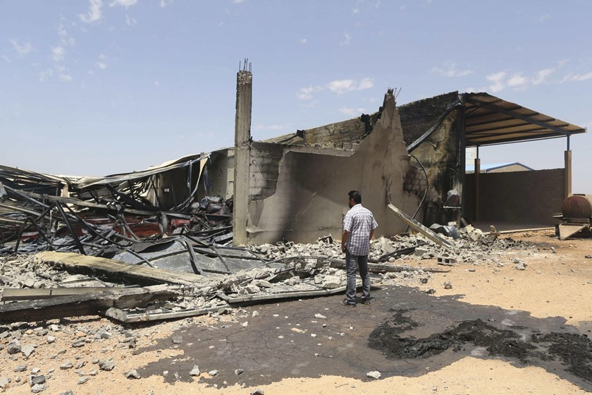 File photo: A man looks at destroyed warehouses following Friday's clashes between Libyan irregular forces and Islamist militias in the eastern city of Benghazi on May 17, 2014